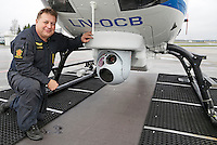 Norwegian Police Helicopter <br /> System operator Lasse Iversen with camera system, mounted underneath the helicopter.