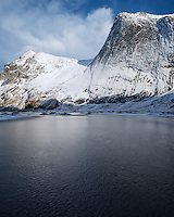 Steep snow covered granite cliffs of Helvetestind mountain rises above ice covered Bunes beach, Moskenesøy, Lofoten Islands, Norway
