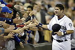 Seattle Mariners Edgar Martinez high fives Mariner fans as he runs the tadck surrounding the infield during Edgar Martinez Day on Saturday, Oct. 2, 2004 in Seattle. Jim Bryant Photo