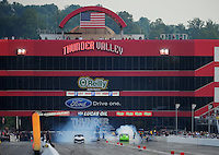 Jun. 18, 2011; Bristol, TN, USA: NHRA pro mod driver Leah Pruett-LeDuc (left) does a burnout alongside Chip King during qualifying for the Thunder Valley Nationals at Bristol Dragway. Mandatory Credit: Mark J. Rebilas-