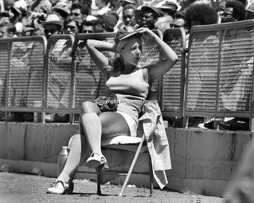 Oakland Athletics ball girl Mary Barry sitting along the foul line at the Oakland Alameda County Coliseum during A's game. (1972 photo by Ron Riesterer)