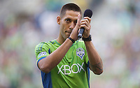 Clint Dempsey applauds the crowd after being introduced as a Sounder before a game against the Sounders FC and FC Dallas at CenturyLink Field in Seattle Saturday August, 3, 2013. The Sounders defeated Dallas 3-0.