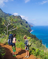 Two backpackers pause to look at the coastline on the Kalalau Trail on Kaua'i.