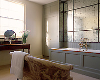 A small sofa upholstered in toile de Jouy fabric has been placed opposite the panelled bath in this spacious bathroom