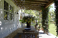 A rustic table and bench have been placed in the shade of a large covered porch to one side of the house, ideal for informal outdoor dining