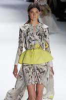 Jacquelyn Jablonski walks runway in a White psychedelic printed stretch cotton hooded long sleeve pullover and yellow super pique peplum drawstring belt, White psychedelic printed chiffon carved hem skirt, by Vera Wang, for the Vera Wang Spring 2012 collection, during Mercedes-Benz Fashion Week Spring 2012.