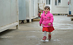 """A displaced girls walks among """"caravans,"""" manufactured housing units for displaced families, in the village of Bakhtme, Iraq. The community was flooded with displaced families when the Islamic State group took over nearby portions of the Nineveh Plains in 2014. The community includes a """"child-friendly space"""" sponsored by the Christian Aid Program Nohadra - Iraq (CAPNI), offering displaced children and children from the host community an opportunity to play and learn."""