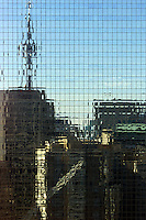 CN Tower and other buildings reflected in mirror surface of building across the street in Toronto.