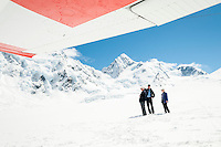 Tourists enjoying pristine upper parts of Tasman Glacier on ski plane landing, Aoraki Mt. Cook National Park, Mackenzie Country, South Island, New Zealand