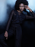Beautiful african american woman wearing fashionable black clothes posing on shiny black background. High fashion photo.