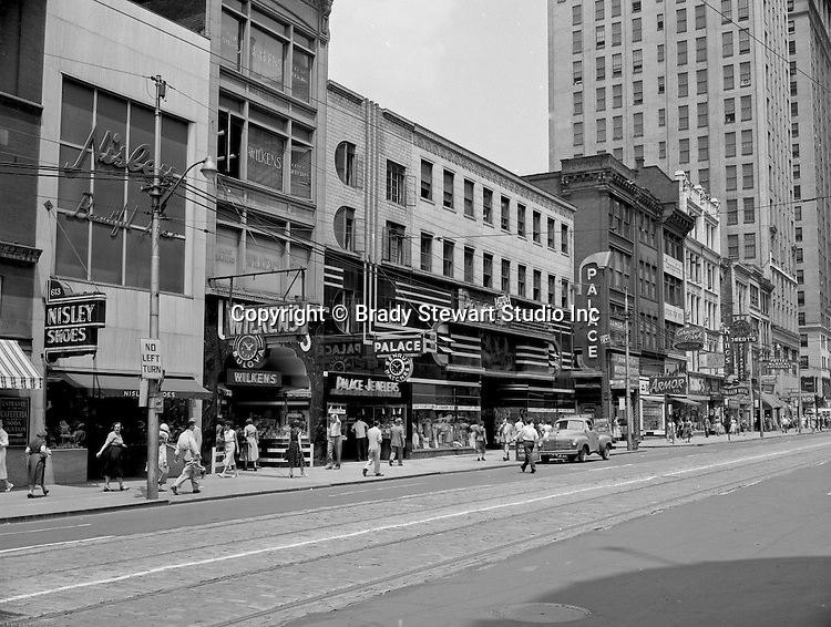 Pittsburgh PA:  View east on Liberty Avenue toward Pennsylvania Railroad Station - 1950s.  Businesses on the north side (600 block) of the street include: Nisley Shoes, Wilkens Jewelers, Palace Jewelers, Armor Modern Kitchens, Carnegie Park Mens store, Isalys Deli, Kings Clothing Store, Lomakin Music, Robert's Restaurant & Bar, Pettey Musical Instruments, and Western Union.