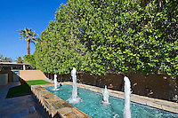 Water feature is seen amid landscaped hedge, lawn and stone patio