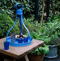 A blue Patmos tray, designed by John Stefanidis, laden with coloured glasses stands on a garden table