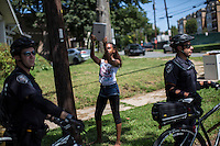 A girl takes a photo with an iPad as police keep watch over the March on Wall Street South protest on Sunday, September 2, 2012 in Charlotte, NC.