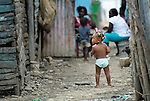 A young child walks along a street in Batey Bombita, a community in the southwest of the Dominican Republic whose population is composed of Haitian immigrants and their descendents.
