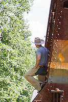 rugged handsome cowboy outdoors standing on a railroad trestle