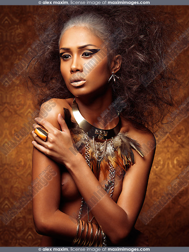Exotic beauty portrait of a young beautiful woman with bird theamed styling, feathery necklace and accessories in shiny golden colors