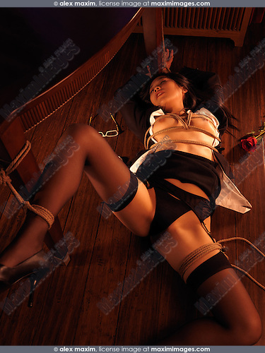 Sexy young asian woman lying down on the floor tied with Japanese rope bondage Shibari