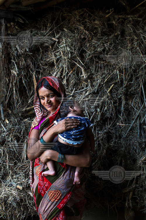 22 year old Seema Devi with her three month old son, Krishna in the courtyard of their hut in Khurmaniya village. Seema Devi lost five of her children and her sixth child, Krishna, was born in a government hospital. She is doing everything to make sure her son stays healthy.
