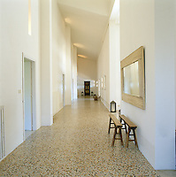 In a corridor of this converted schoolhouse in Tuscany the multi-coloured terrazzo flooring creates a pleasing visual contrast with the monastic white walls and the hand-painted door from Lombok at the far end