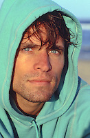 man with blue eyes in a hooded sweatshirt at the beach