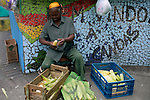 South America, Brazil. Rio de Janiero. Woman husking corn on corner in Favela of Vila Canoas.