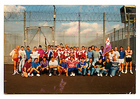 A photograph of Tommy and friends inside the Maze prison in the 1990s. (The Maze prison, on the site of a former Royal Airforce station of Long Kesh on the outskirts of Lisburn in Northern Ireland was used during the Troubles (a period of intercommunal violence and strife which lasted for approximately 3 decades from the 1960s to 1998, when the Good Friday Agreement ended outright hostilities) to house paramilitary prisoners. It was closed in 2000 and partly demolished.) On the reverse a handwritten message written by Tommy's daughter Angela when she was a child reads: 'Men and My Daddy.'.