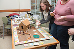 Graduate College Student Services employee Maggie DeLong helps construct her department's entry into this year's gingerbread house competition. Photo by Ben Siegel