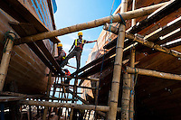 Ecuadorian shipbuilding workers provide maintenance to the traditional wooden fishing vessels in an artisanal shipyard on the beach in Manta, Ecuador, 8 September 2012. The construction process takes 3-4 months to complete, depending on the ship size and purpose (fish capture methods). Although a wooden boat tends to be more stable on the sea and less expensive to build (up to $0.5 million USD), it needs a maintenance every 2 years, while a fiberglass-made boat, costing almost double the wooden one, may serve 5-6 years without any repairs. The shipyard produces 6-8 vessels every year.