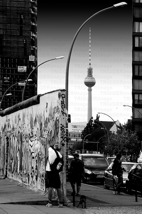 Tourists photographing a piece of the Berlin Wall at the East Side Gallery in Berlin.