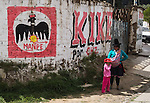 """On July 4, 2014, a campesino woman and child stands by a wall plastered with a sign for political candidate """"KIKE"""" of the neo-Nazi MANPE party, in the Santa Valley (or Callejon de Huaylas) in the Ancash Region in the north-central highlands of Peru, South America. Historically, high poverty rates (as found in Peru) can foster extremist political factions such as Peru's neo-Nazi MANPE (Movimiento de Accion Nacionalista Peruano): Peruvian Nationalist Action Movement)."""