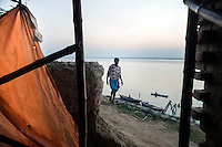 A man walk passes a temporary shelter broken due to a recent storm at Kulidihar village in West Bengal, India.