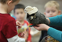 NWA Democrat-Gazette/DAVID GOTTSCHALK  The hands of Sherry Rodgers (right), children's librarian for the Washington County Library System, holds a raccoon hand puppet Wednesday, February 15, 2017, as Jude Abshier, 4, attempts to tie it's shoelaces during the Getting Dressed themed Spring Story Time at the Lincoln Public Library. Spring Story Time for the library system runs through May 19 presenting programs for ages three and up.