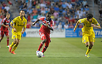 Chicago midfielder Patrick Nyarko (14) dribbles toward the Columbus goal while being pursued by Columbus defender Nemanja Vukovic (32, right).  The Chicago Fire defeated the Columbus Crew 2-1 at Toyota Park in Bridgeview, IL on June 23, 2012.