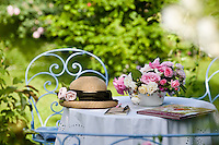 A bowl of freshly cut roses and a woman's sun hat on the table covered with a white tablecloth in a secluded spot in the rose garden