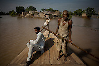 Reduced to islands, men are forced to use the few available boats to get to and from their homes - millions have been forced from their homes and even after a month since the flooding water remains in place with no sign of receeding.