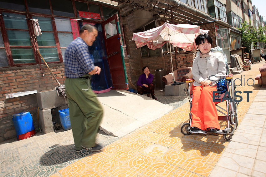 A neighbor walks pass Li Yan sitting in her wheel-chair in a residence in Yinchuan, Ningxia Province, China, on May 7, 2007. 28-year-old Li Yan suffers from motor neuron disease also known as amyotrophic lateral sclerosis (or ALS), the same illness that has thereotical physicist Stephen Hawking. Li Yan asked China's National People's Congress (NPC) to consider a draft on euthanasia. Photo by Lucas Schifres/Pictobank