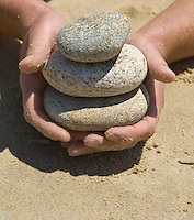 Hands holding stack of rounded stones