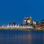 The lights of Canada Place, the Trade and Convention Center and other downtown buildings reflect on the water of Coal Harbour during the early evening in Vancouver, British Columbia, Canada