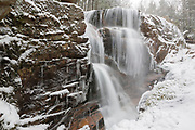 Franconia Notch State Park - Avalanche Falls in Lincoln, New Hampshire USA during a snow storm. This waterfall is located in the Flume Gorge. Blowing snow can be seen in the image.