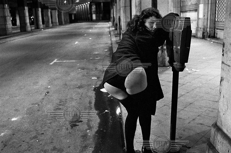 A transsexual prostitue flashing her bottom while leaning on a parking meter.