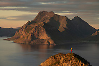 Female hiker on summit of Hornet with mountains of Vestvågøy rising across sea in distance, Flakstadøy, Lofoten Islands, Norway