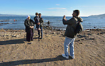 A refugee photographs other refugees on a beach near Molyvos, on the Greek island of Lesbos, on November 3, 2015. They arrived on a boat full of refugees from Turkey. They were received by local and international volunteers, then proceeded on their way toward western Europe. The boat was provided by Turkish traffickers to whom the refugees paid huge sums to arrive in Greece.