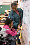 Oakland CA Developmentally disabled primary school student in wheelchair learning to read with aide's help in special education classroom  MR