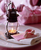 A delicate place setting with a tealight in a miniature lantern and rock candy