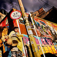 A Colombian street vendor walks around a street corner, covered in colorful graffiti artwork and posters, in La Candelaria, Bogota, Colombia, 19 February, 2016. A social environment full of violence and inequality (making the street art an authentic form of expression), with a surprisingly liberal approach to the street art from Bogotá authorities, have given a rise to one of the most exciting and unique urban art scenes in the world. While it's technically not illegal to scrawl on Bogotá's walls, artists may take their time and paint in broad daylight, covering the walls of Bogotá not only in territory tags and primitive scrawls but in large, elaborate artworks with strong artistic style and concept. Bogotá has become an open-air gallery of contemporary street art.