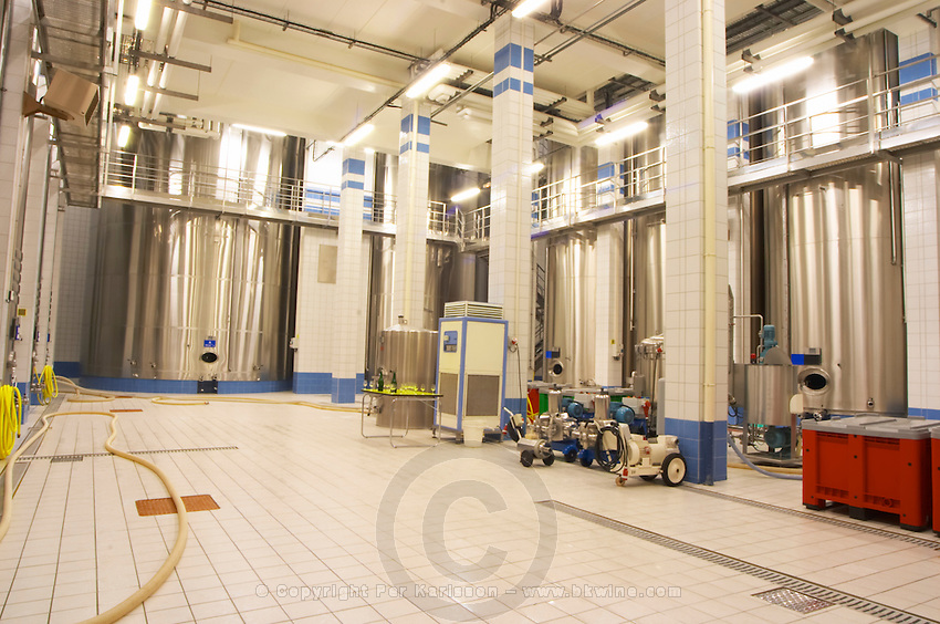 In the winery: The main blending room with several big stainless steel blending and fermentation tanks and the floor and walls covered in white and blue tiles. In the middle: pumps, filters and cooling units, the Union Champagne cooperative, also called Champagne de Saint Gall in Avize, Cote des Blancs, Champagne, Marne, Ardennes, France