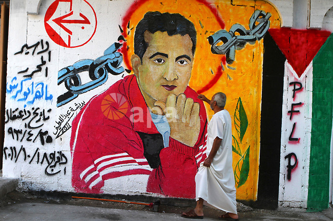 Relatives of Palestinian prisoner, Maher Abu Karesh stand near a graffiti depicting his picture as they gather at his house in the Gaza Strip on 17 October 2011 as they await his release as part of a deal to secure the exchange of Israeli captive soldier Gilad Shalit. Under a prisoner swap deal signed with Israel, Hamas will free Shalit, held in Gaza since 2006, in exchange for 1,027 Palestinian prisoners. Photo by Ashraf Amra