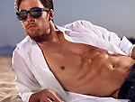 Muscular sexy young man in unbuttoned shirt lying on sand at the beach