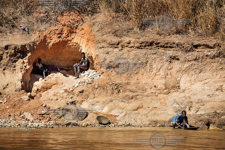 A gold panner, working in the Tsiribihina River, is watched by colleagues as he works in the hot sun.